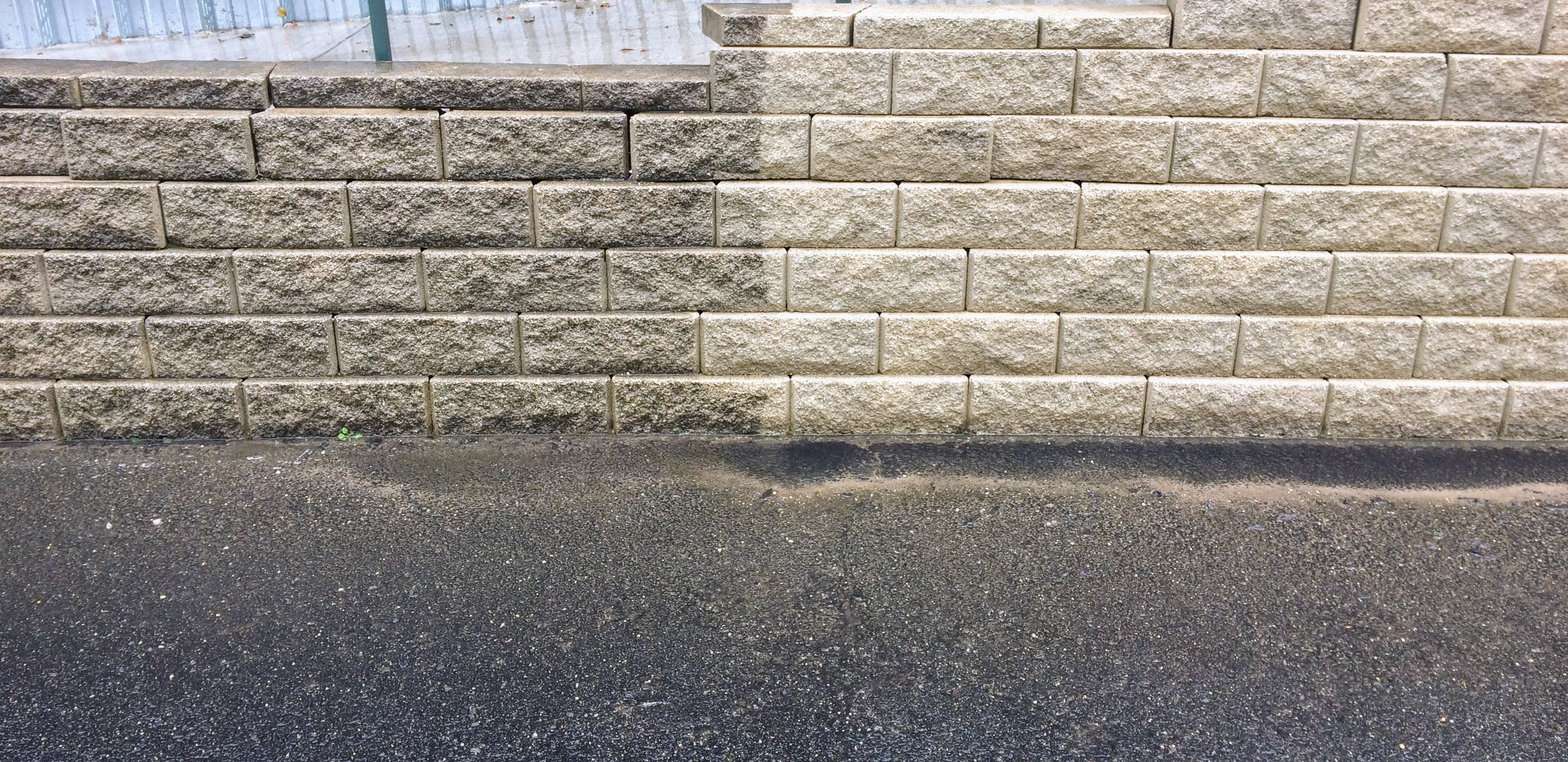 Retaining wall that has been power washed revealing the extent of dirt and grime.
