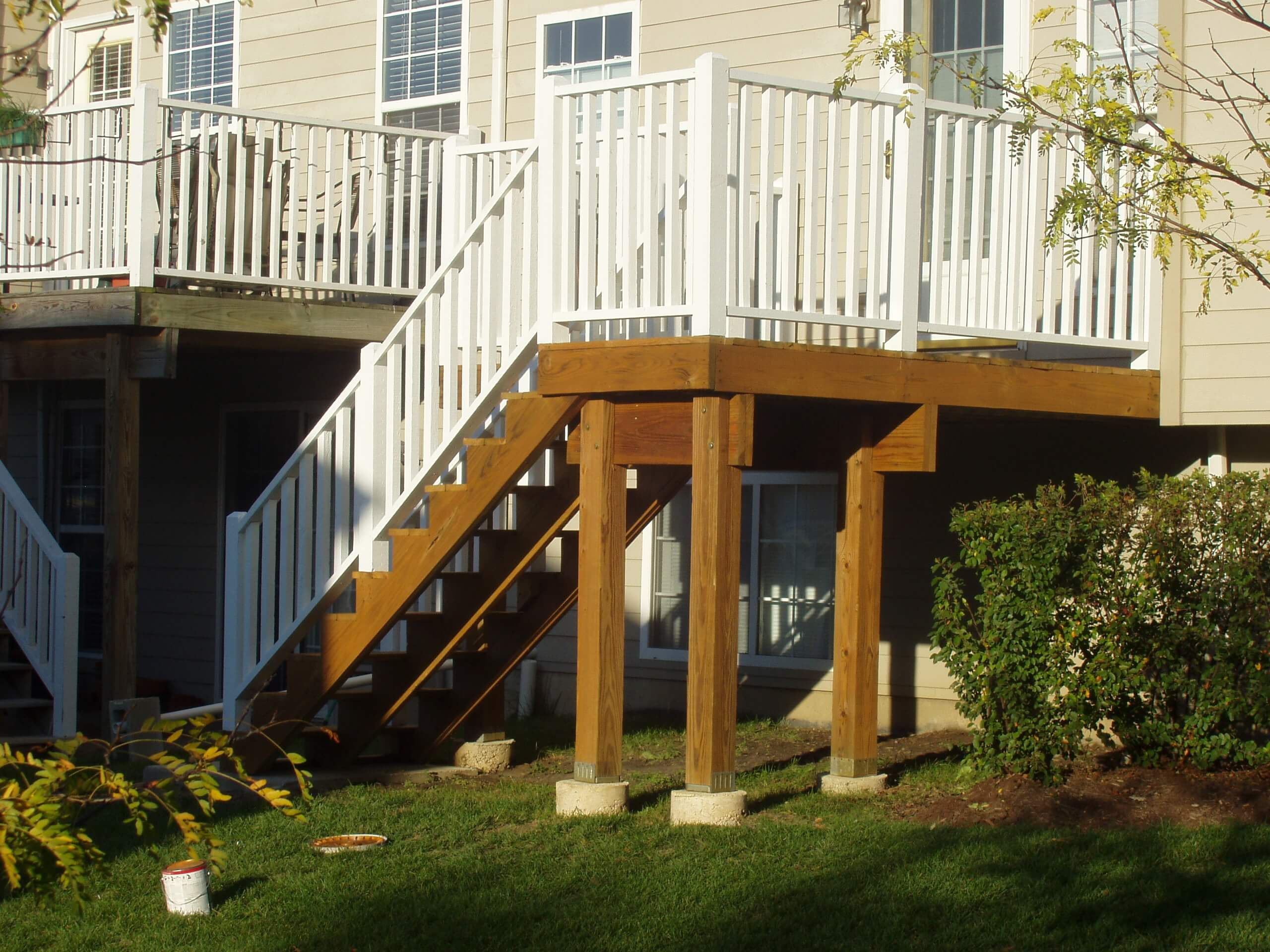 Raised deck with steps. Deck floor and posts stained with transparent cedar and white railings.