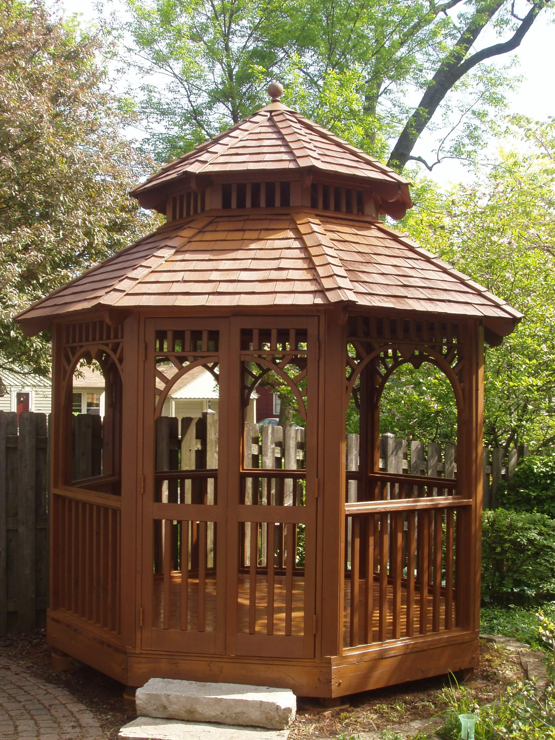 Outdoor gazebo recently stained with a semi transparent cedar bark stain and trees in the background.