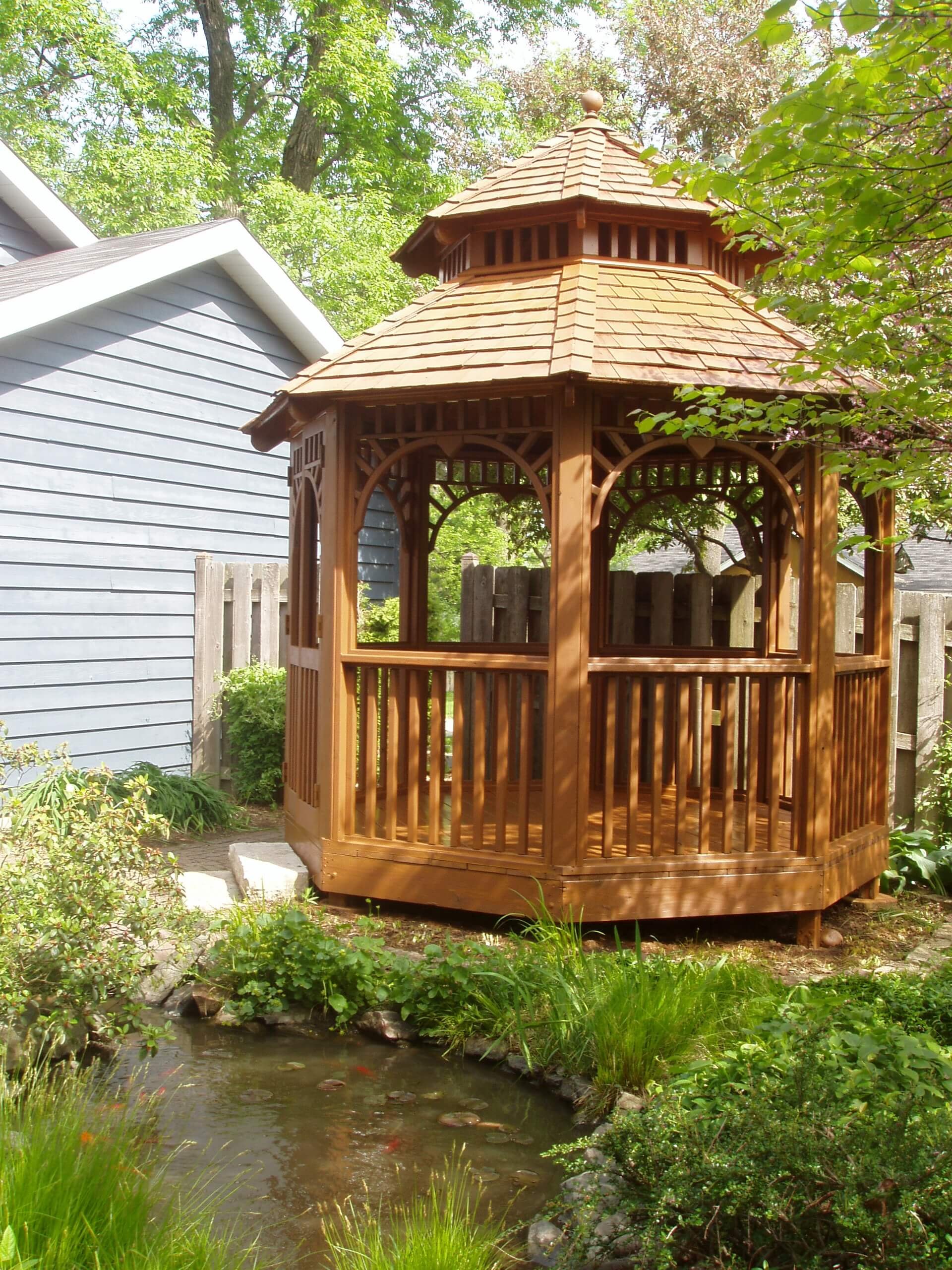 Outdoor gazebo that has recently been treated and is located adjacent to a pond