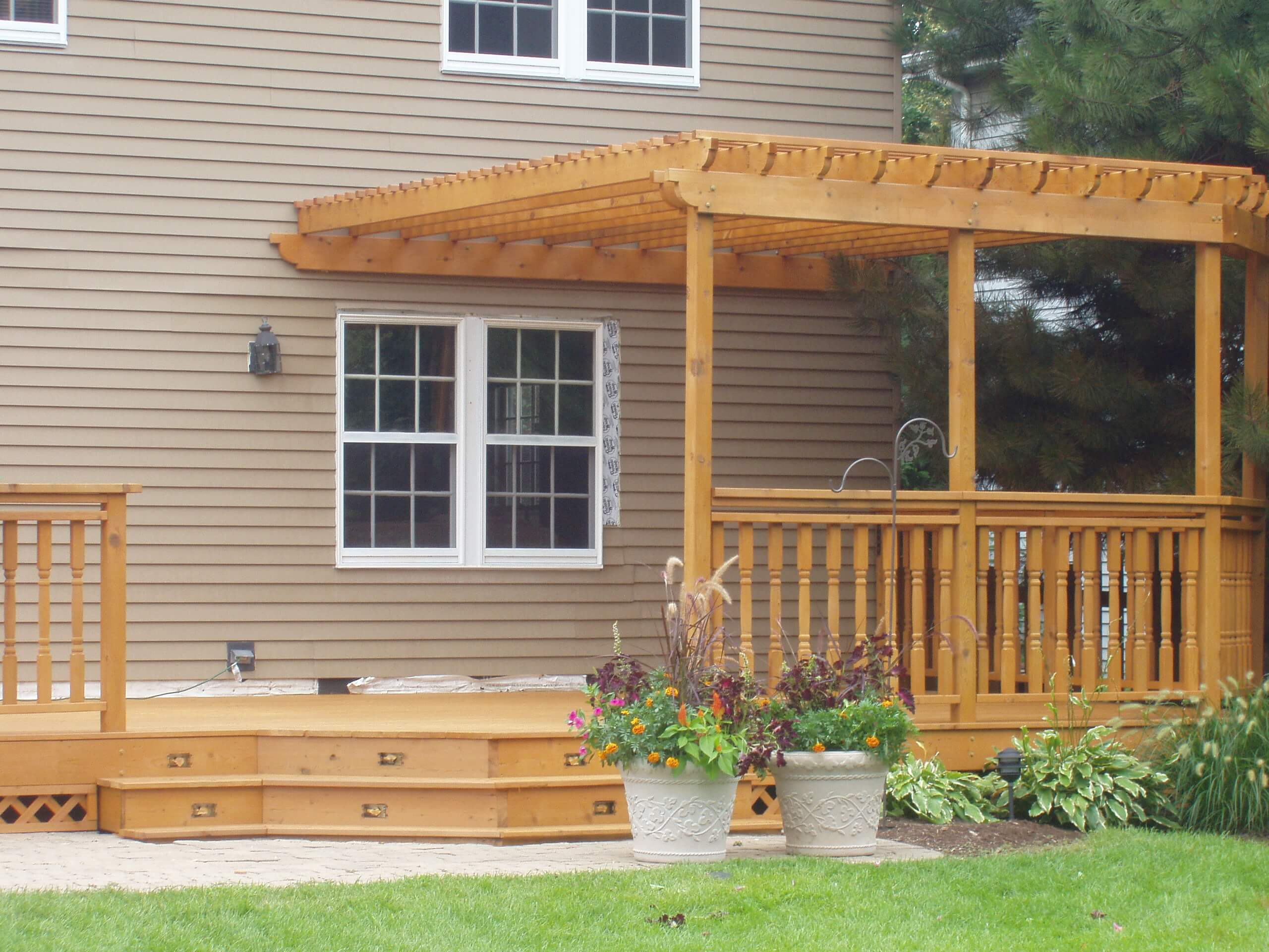 Cedar deck with pergola attached to the house which has recently been stained with a transparent cedar stain.