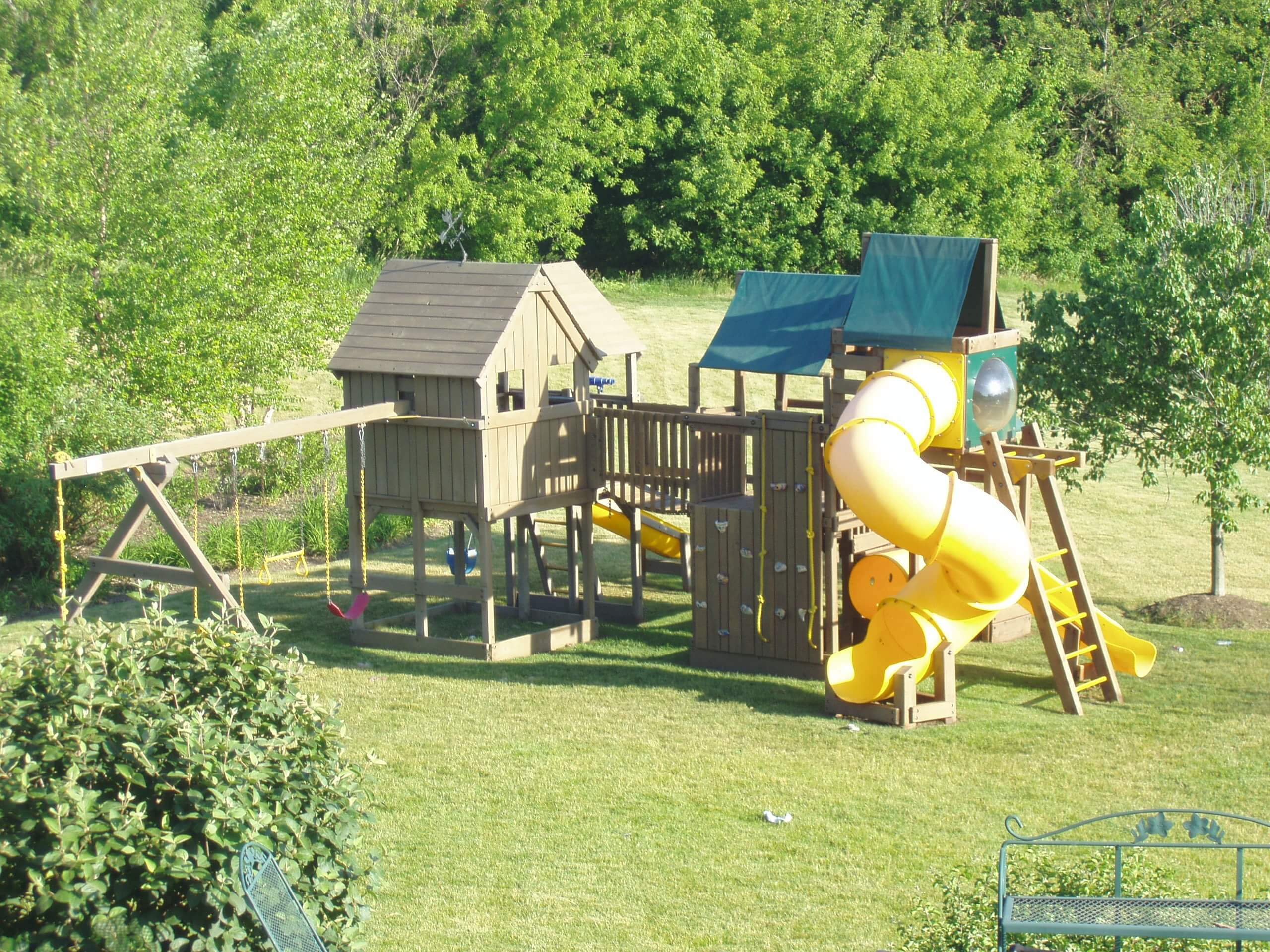Large outdoor playset with slides and swings that has recently been stained with a semi transparent green colored stain.