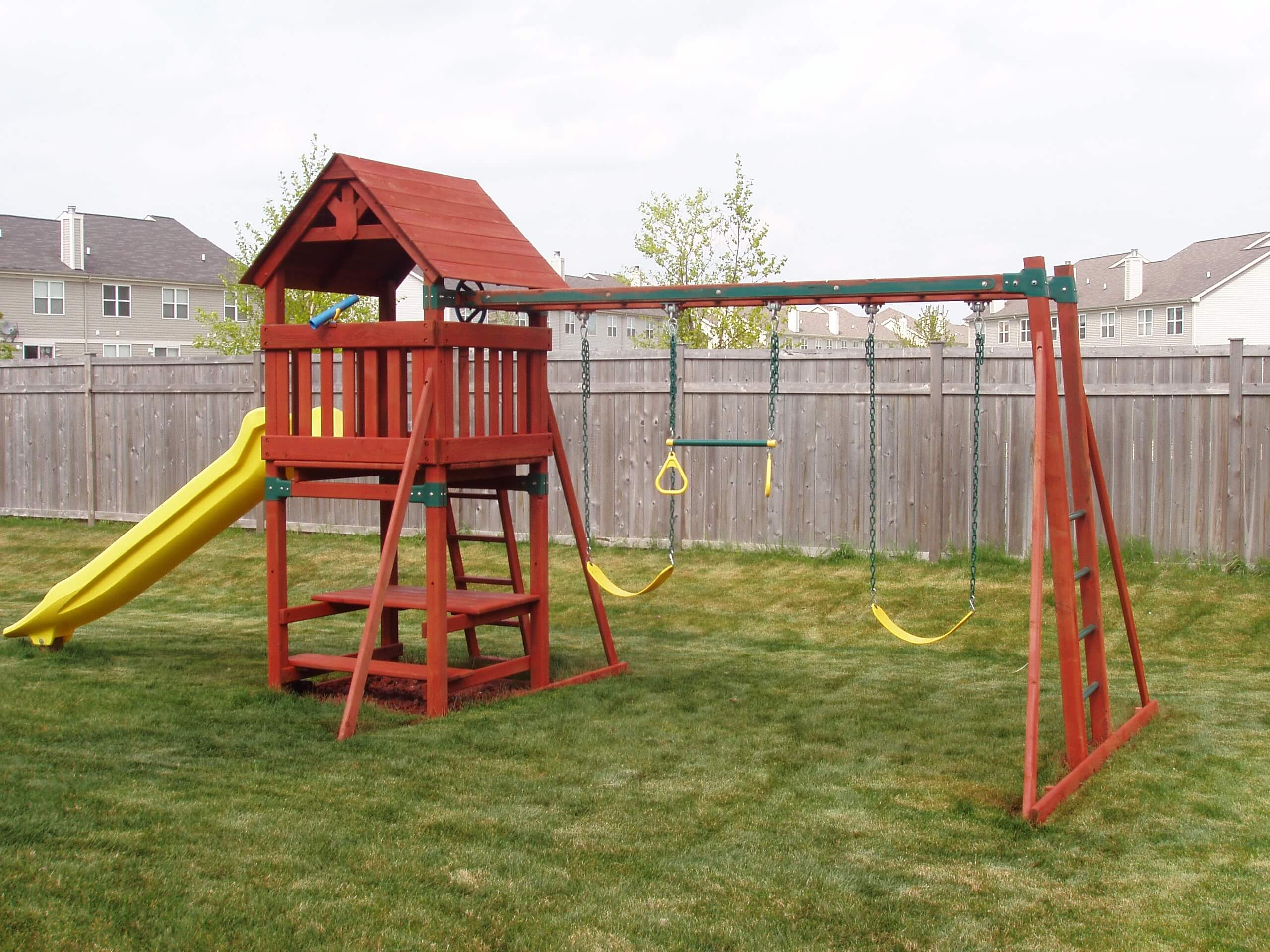 Outdoor playset with swings and slide that has recently been stained with a semi transparent red stain.