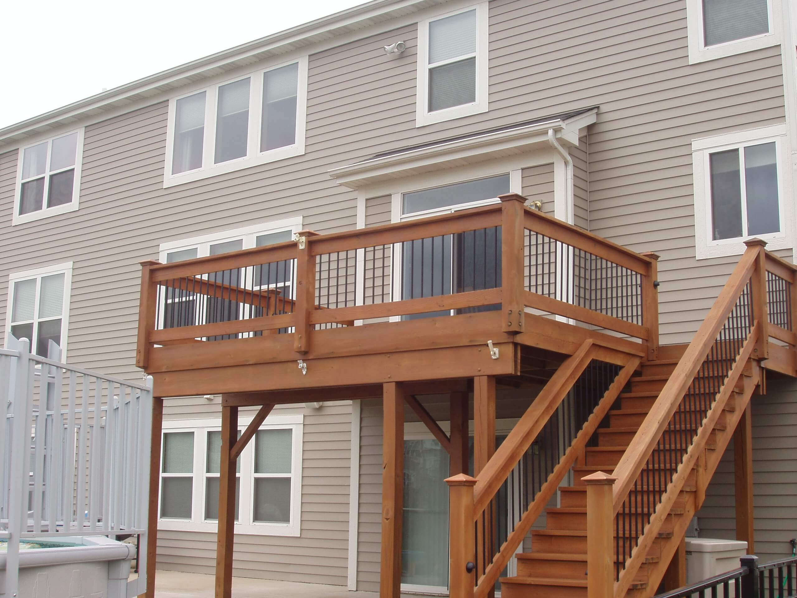 Raised deck with metal spindles that was recently cleaned, sanded, stained and sealed with a transparent cedar stain.