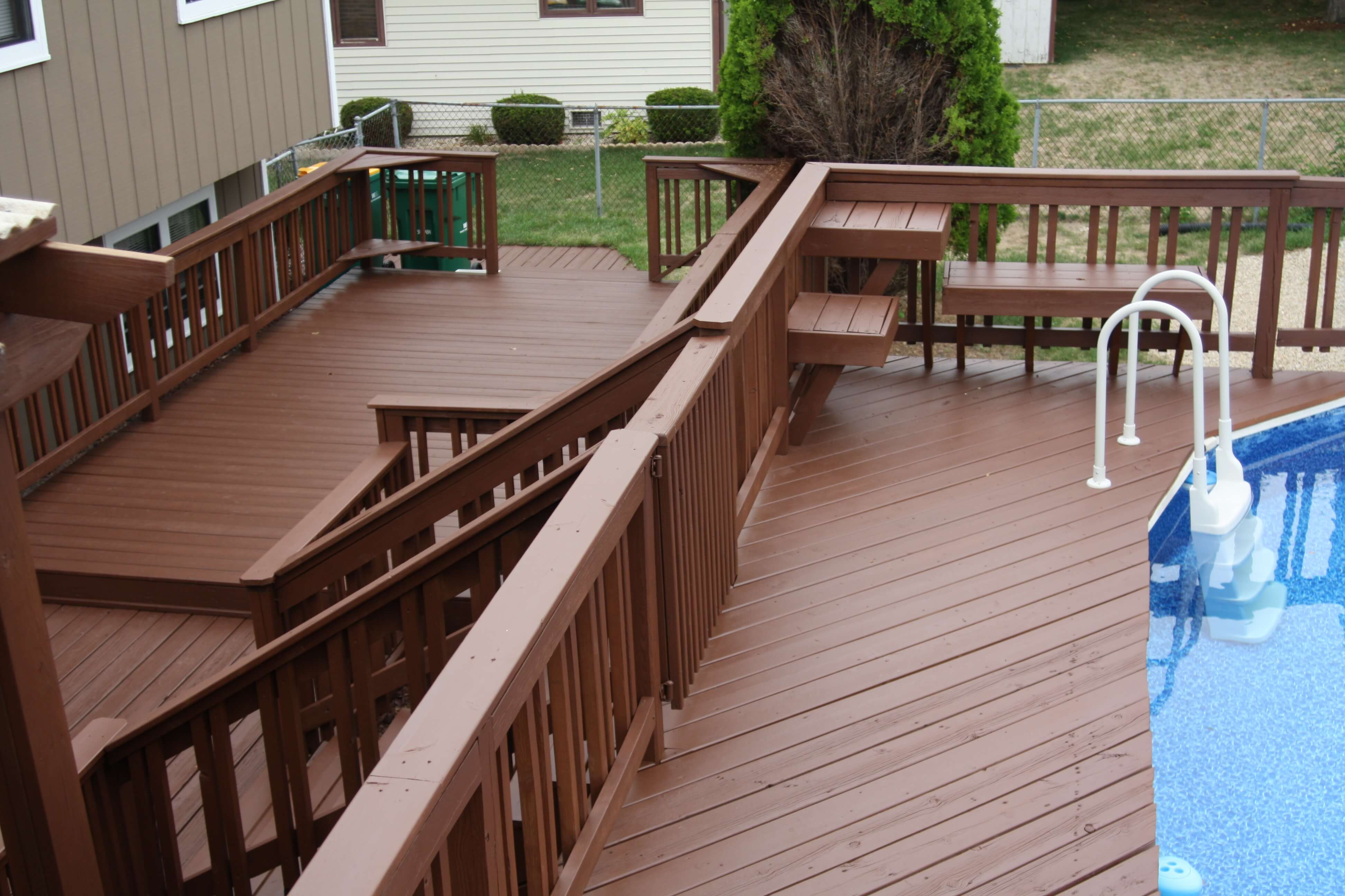 Bi-level deck adjacent to a pool. Treated with a dark semi transparent stain.