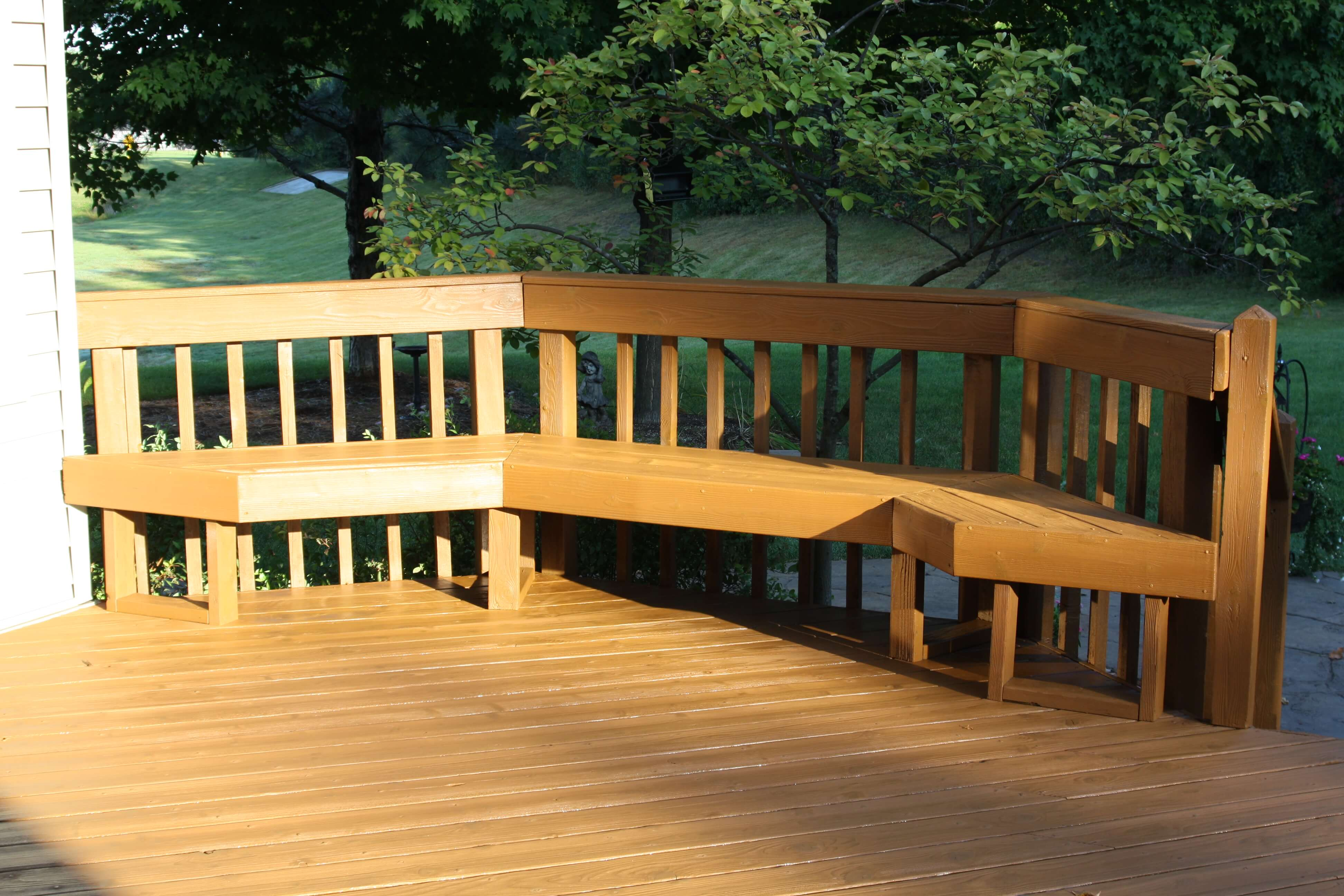 Seating area of a raised deck that has recently been stained with a semi transparent cedar stain.