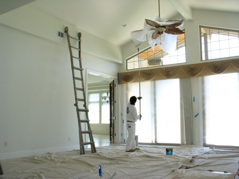 Worker applying paint high on the walls of a home