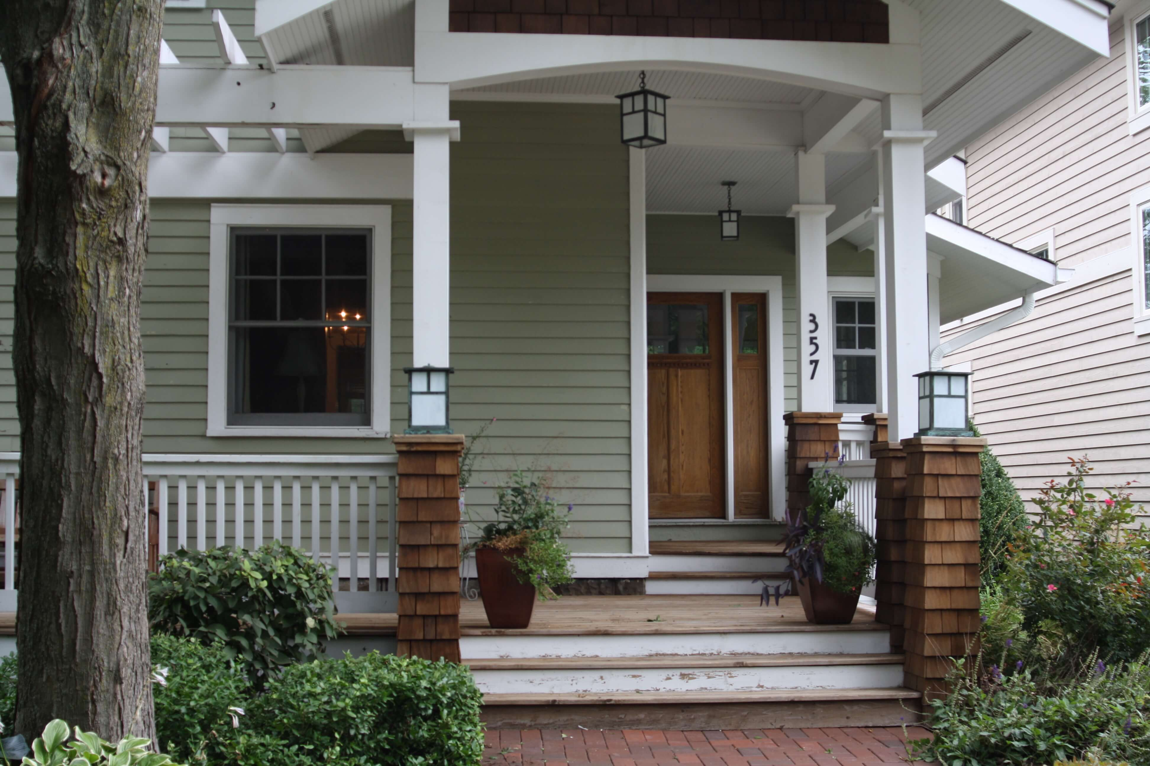 Front entrance to a house with white columns and cedar shake bases