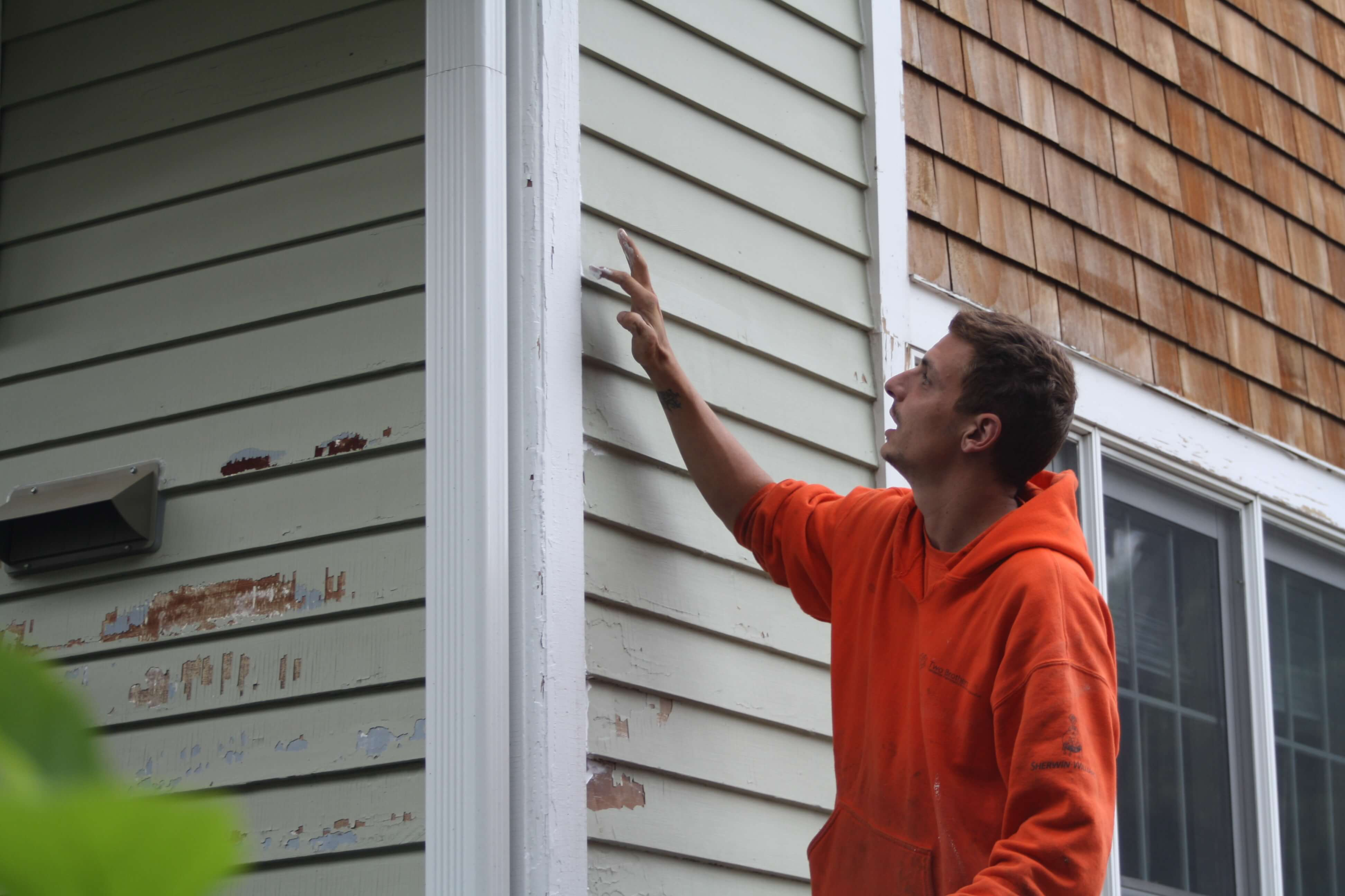 Worker applying caulk to the exterior trim of a house