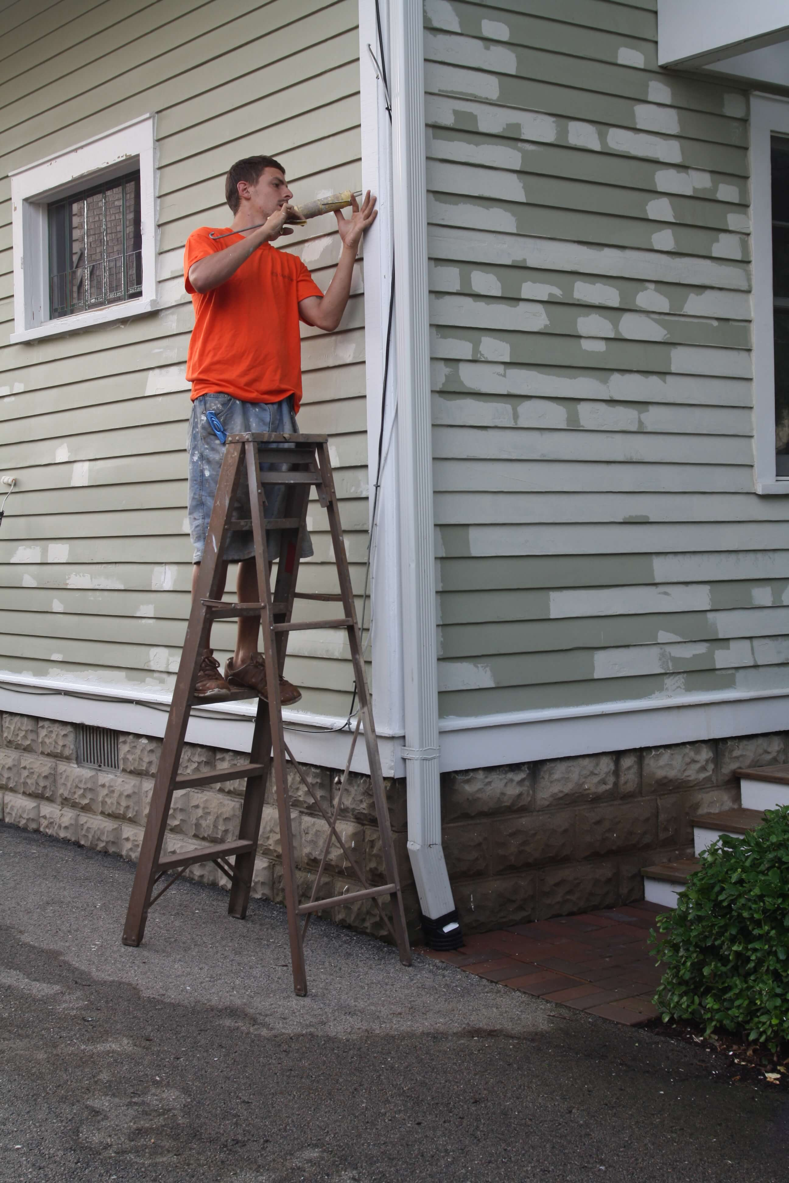 Worker adding caulk to the exterior trim of a house