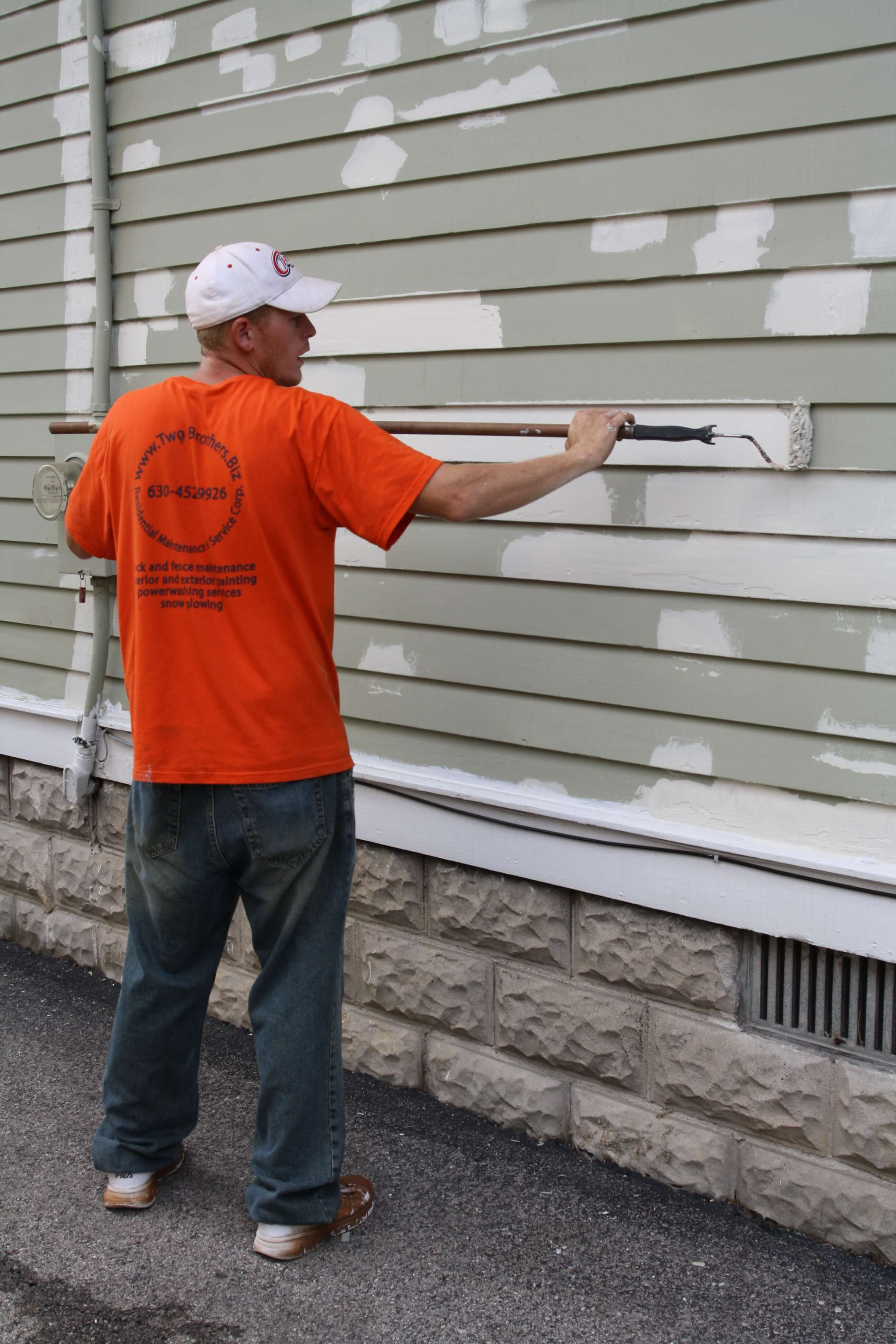 Worker applying paint to cedar siding with a roller