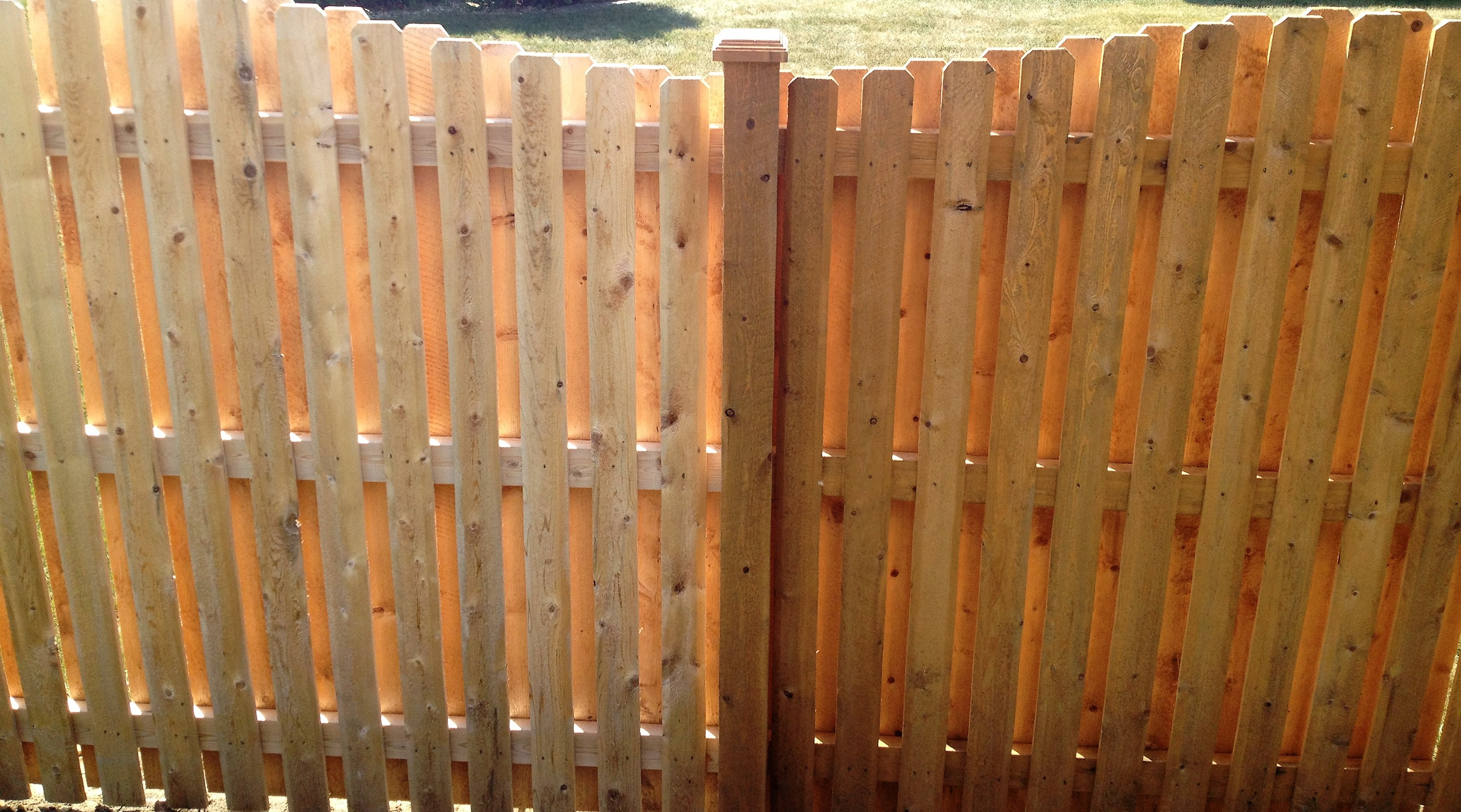 Before and after of Fence receiving a transparent stain.